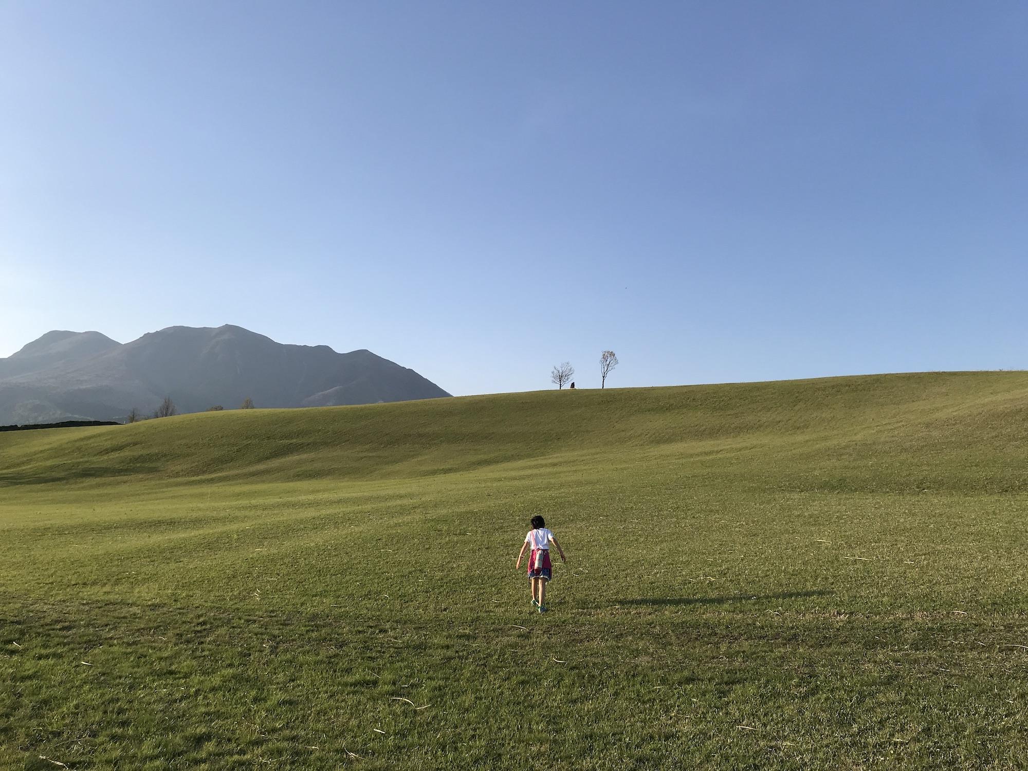 広く平らな緑の大地と青い空の真ん中に女の子が一人