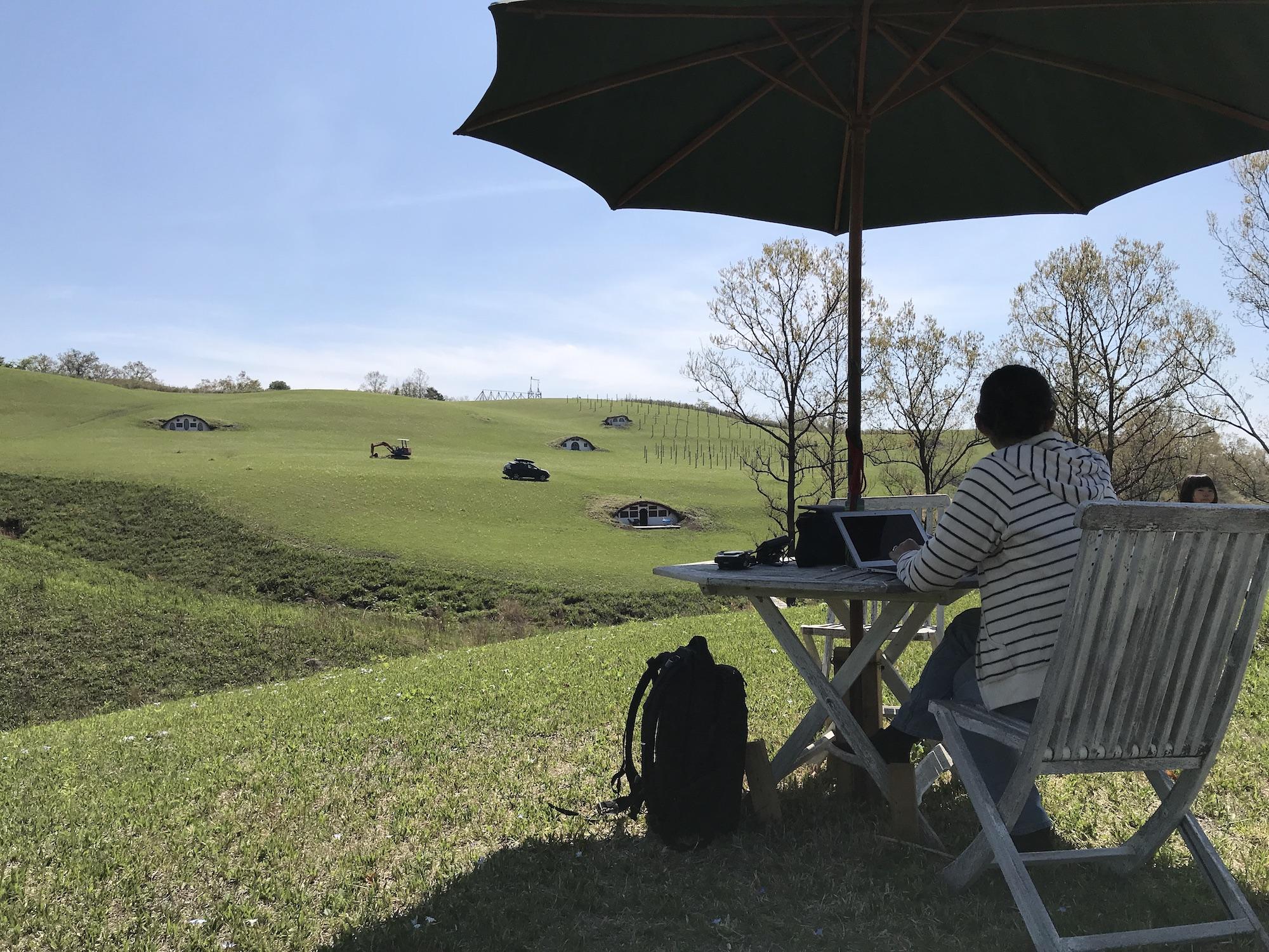 農場に置かれたテーブルで女性がPCを開いて仕事をしている。