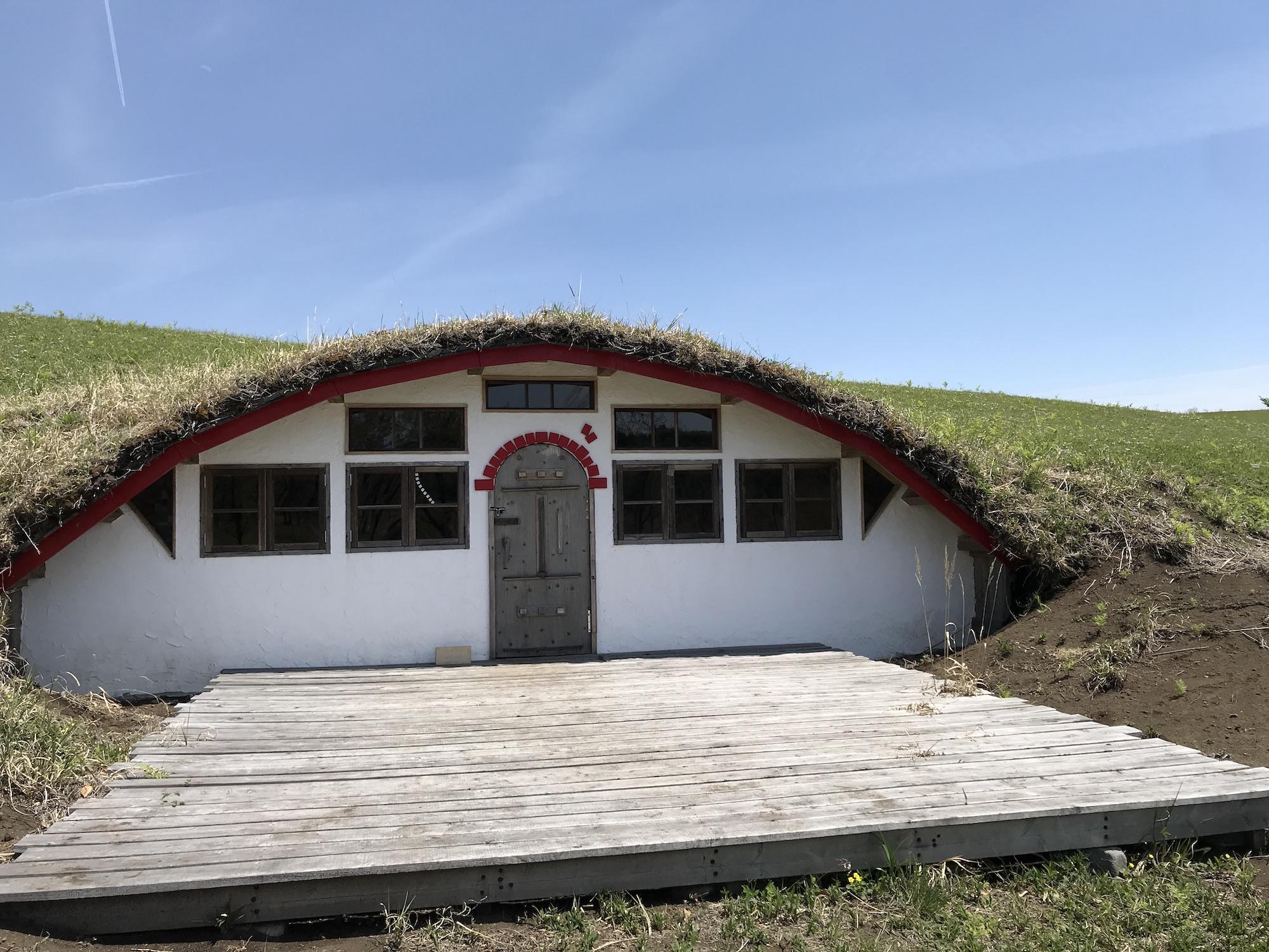 ホビットが住んでいそうな横穴式おうち。白い壁に窓が7つ。屋根は赤で縁取られている。